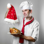 Chef showing plate with chicken and Santa hat — Stock Photo