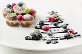Cupcakes with fresh berries and sweet christmas tree — Stock Photo