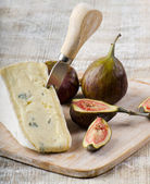 Cheese and figs on wooden platter — Stock Photo
