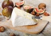 Cheese on wooden platter — Stock Photo