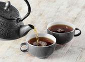 Té se vierte en la taza de té — Foto de Stock