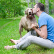 Happy man and his dog in summer - Stock Photo