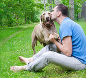 Happy man and his dog in summer — Stock Photo