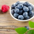 Blueberries and raspberry on wooden table — Stock Photo #28722491