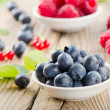 Blueberries and raspberry on wooden table — Stock Photo