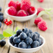 Blueberries and raspberry on wooden table — Stock Photo #28722929