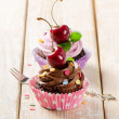 Stock Photo: Cupcakes with cherry on a wooden table