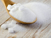 Sugar on wooden table — Stock Photo