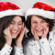 Young happy smiling girls in Santa hats — Stock Photo