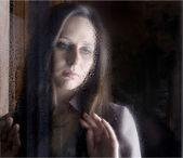 Kvinna som tittar genom fönstret — Stockfoto