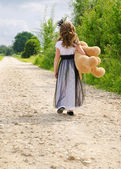 Little girl walking on the road in summer. — Stock Photo