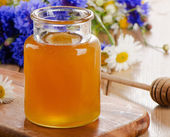 Honey Jar with wooden stick — Stock Photo