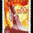 DEMOCRATIC PEOPLES REPUBLIC (DPR) of KOREA -CIRCA 1980: A stamp printed in DPR Korea (North Korea) shows hand compressing a butt of a rifle, circa 1980 — Stock Photo #12165315