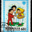 MONGOLIA - CIRCA 1980: A stamp printed in Mongolia shows boys give flowers to girl, circa 1980 — Stock Photo