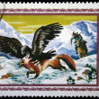 Foto de Stock  : MONGOLI- CIRC1975: stamp printed in Mongolishows cleavage at forefront of attacking red fox, hunter in middle ground, leaping on his horse, mountains in background, circ1975