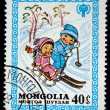 MONGOLIA - CIRCA 1980: A stamp printed in Mongolia shows girl on sled and boy on ski, circa 1980 — Stock Photo