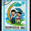 MONGOLIA - CIRCA 1980: A stamp printed in Mongolia shows pioneer holding umbrella under a girl, circa 1980 — Stock Photo
