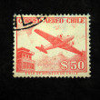 Stock Photo: CHILE - CIRC1950s: stamp printed in Chile shows plane on background of building, circ1950s
