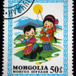 Royalty-Free Stock Photo: MONGOLIA - CIRCA 1980: A stamp printed in Mongolia shows playful girl and boy, circa 1980