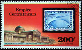 CENTRAL AFRICAN EMPIRE - CIRCA 1977: A stamp printed in Central African Empire (in present time Republic) shows postage stamp of airship on background of Museum of Sciense and Industry Chicago, USA, c — Stock Photo
