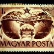 HUNGARY - CIRCA 1950: A Stamp printed in Hungary shows The slogan - Workers of the world unite - against the background of the two hemispheres of the Earth and the bridge over the Danube, circa 1950 — Stock Photo
