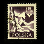 POLAND - CIRCA 1958: A stamp printed in Poland shows skis, stuck in the snow, against the backdrop of snow-capped mountain peaks, circa 1958 — Stock Photo