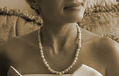 Retro style photo of pearl necklace on the neck of a young woman in an evening dress — Stock Photo