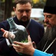 Cossack  tells Orthodox priest about ancient cooking utensil vod - Stock Photo