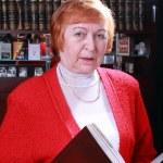 Woman against bookshelf — Stock Photo #21477237
