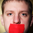 Man closes his mouth red tape — Stock Photo