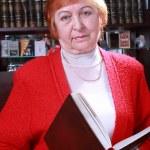 Woman against bookshelf — Stock Photo #21477855