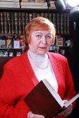 Woman against bookshelf — Stock Photo