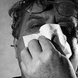 Middle-aged man blowing his nose into a tissue, black and white — Stock Photo