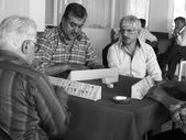Four elderly men play dominos — Stock Photo