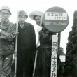 Постер, плакат: Three young men near a sign with the height of Mount Fuji