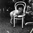 Little boy climbs on white bentwood chair in the garden — Stock Photo