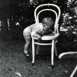 Little boy climbs on white bentwood chair in the garden — Stock Photo #40074861