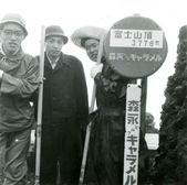 Three young men near a sign with the height of Mount Fuji — ストック写真