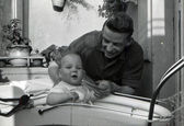 Middle-aged man holding the hand of a child sitting in a Baby transport — Stock Photo