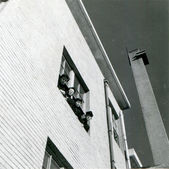 Four men in uniform look out of the window of the second floor — Zdjęcie stockowe