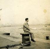Baba deniz izlerken dock üzerinde oturan adam — Stok fotoğraf