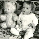 Little boy seats on sofa with Teddy Bear — Stock Photo #40146135