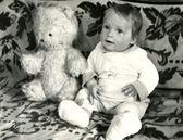 Little boy seats on sofa with Teddy Bear — Stock Photo