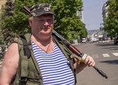 Pro-russian insurgent posing with Kalashnikov during a rally — Stockfoto