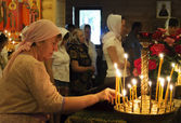 A woman lights a memorial candle — Foto Stock