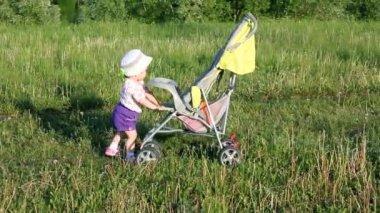 Kind duwt wandelwagen op zomer gazon — Stockvideo
