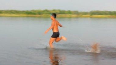 Niño saltando en el lago - lenta — Vídeo de stock