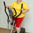 Stock Photo: Overweight womexercising on trainer
