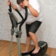 Stock Photo: Overweight man exercising on trainer