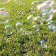 Royalty-Free Stock Vector Image: Soap bubbles flying over green meadow